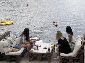 Varias personas en una terraza en el Pantano de San Juan (Madrid).