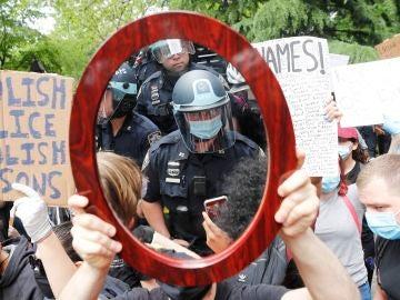 Un oficial de policía de Nueva York reflejado en el espejo de un manifestante