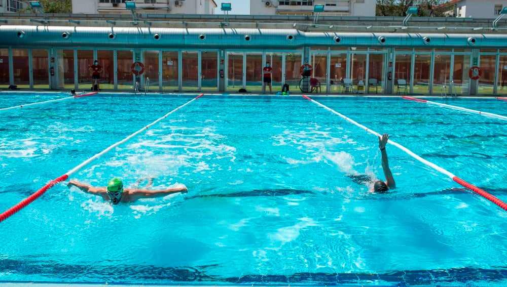 Dos personas nadan en la piscina municipal del barrio sevillano de Tiro de Linea