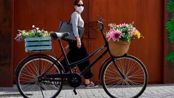 Una mujer con mascarilla pasa junto a una bicicleta aparcada en una calle de Ávila