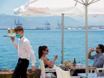 Un camarero con mascarilla pasa ante una pareja que almuerza en un restaurante de Málaga