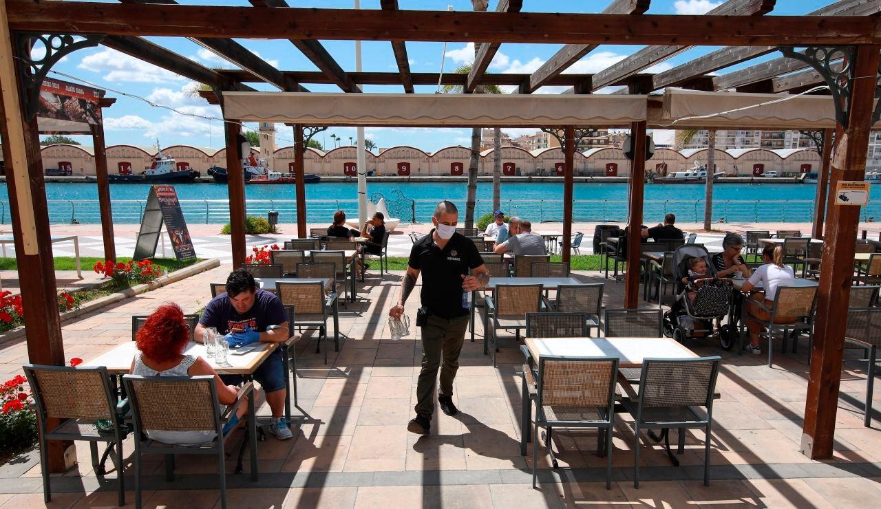 Una terraza con clientes con mascarilla