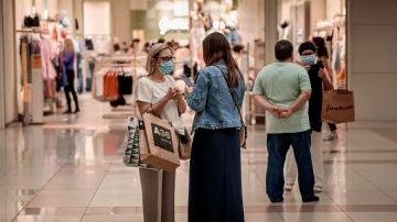 Varias personas realizan compras en un centro comercial con mascarillas.