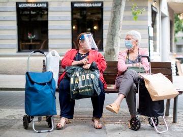 Dos señoras charlan sentadas en un banco del barcelonés barrio de la Sagrada Familia