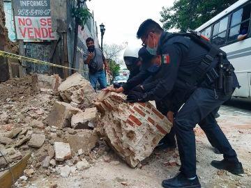Policías y agentes de protección civil retiran escombros de una fachada derruida en Oxaca
