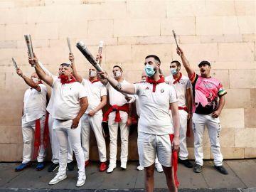 Un grupo de corredores entona los cánticos previos al encierro ante la imagen de San Fermín en Pamplona