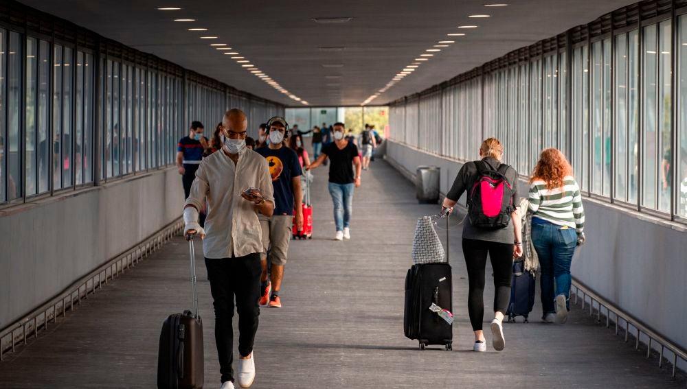Varios pasajeros en uno de los pasillos de la T2 del Aeropuerto de El Prat