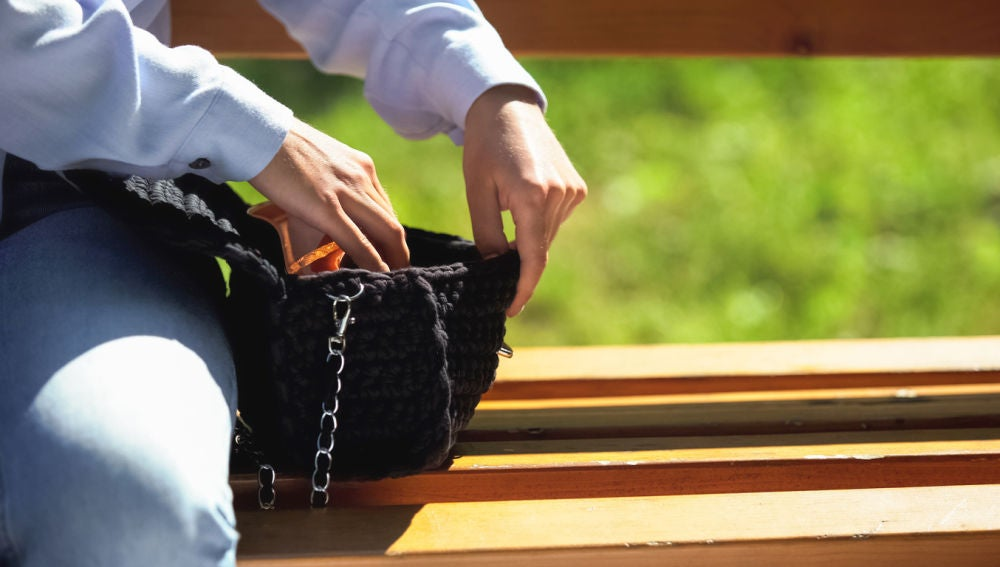 Una mujer revisa su bolso