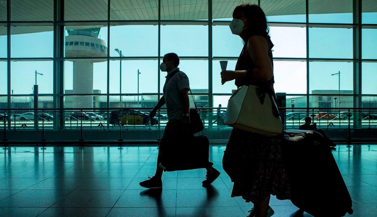Viajeros con mascarillas caminan por  el aeropuerto de El Prat (Archivo)