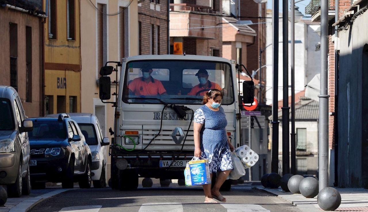 Una mujer pasa por delante de un camión que realiza tareas de desinfección por las calles de Íscar
