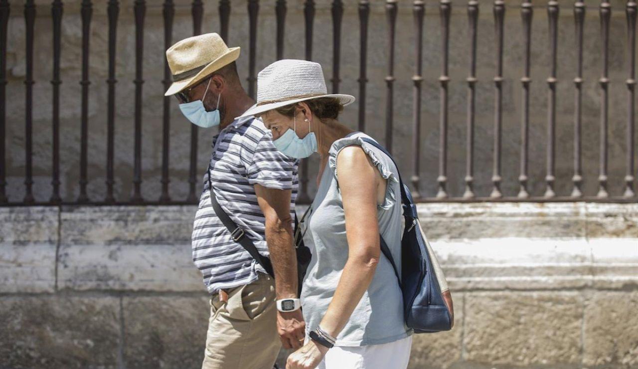 Dos personas caminan con mascarilla y sombrero