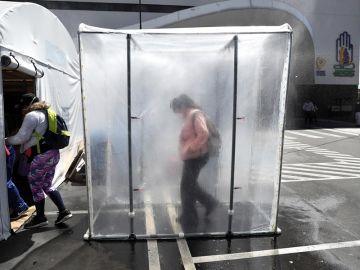 Personas pasan por una cabina de desinfección de coronavirus