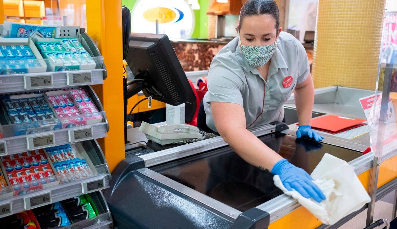 Una empleada de un supermercado desinfecta la caja