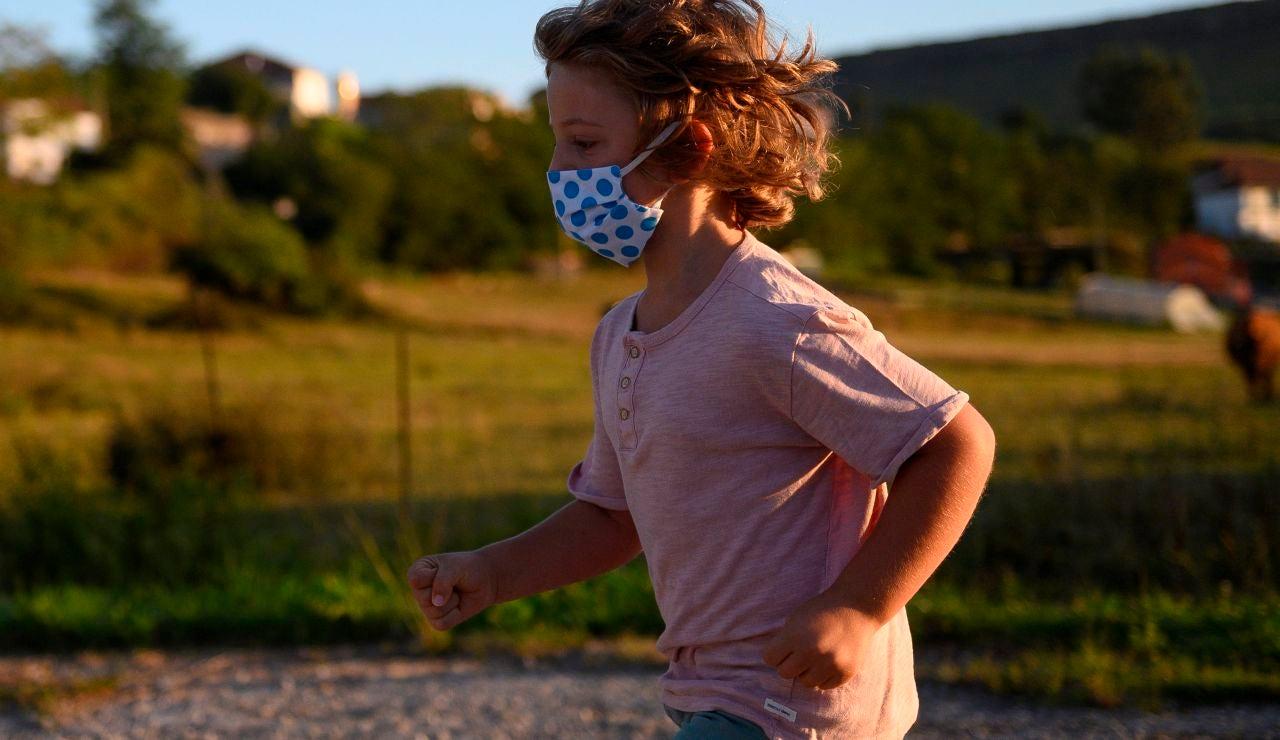 Un niño con mascarilla juega en la calle