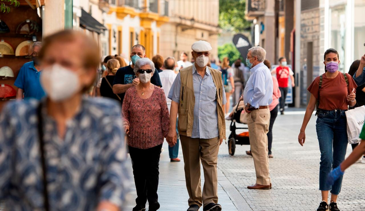 Gente caminando por la calle con mascarilla