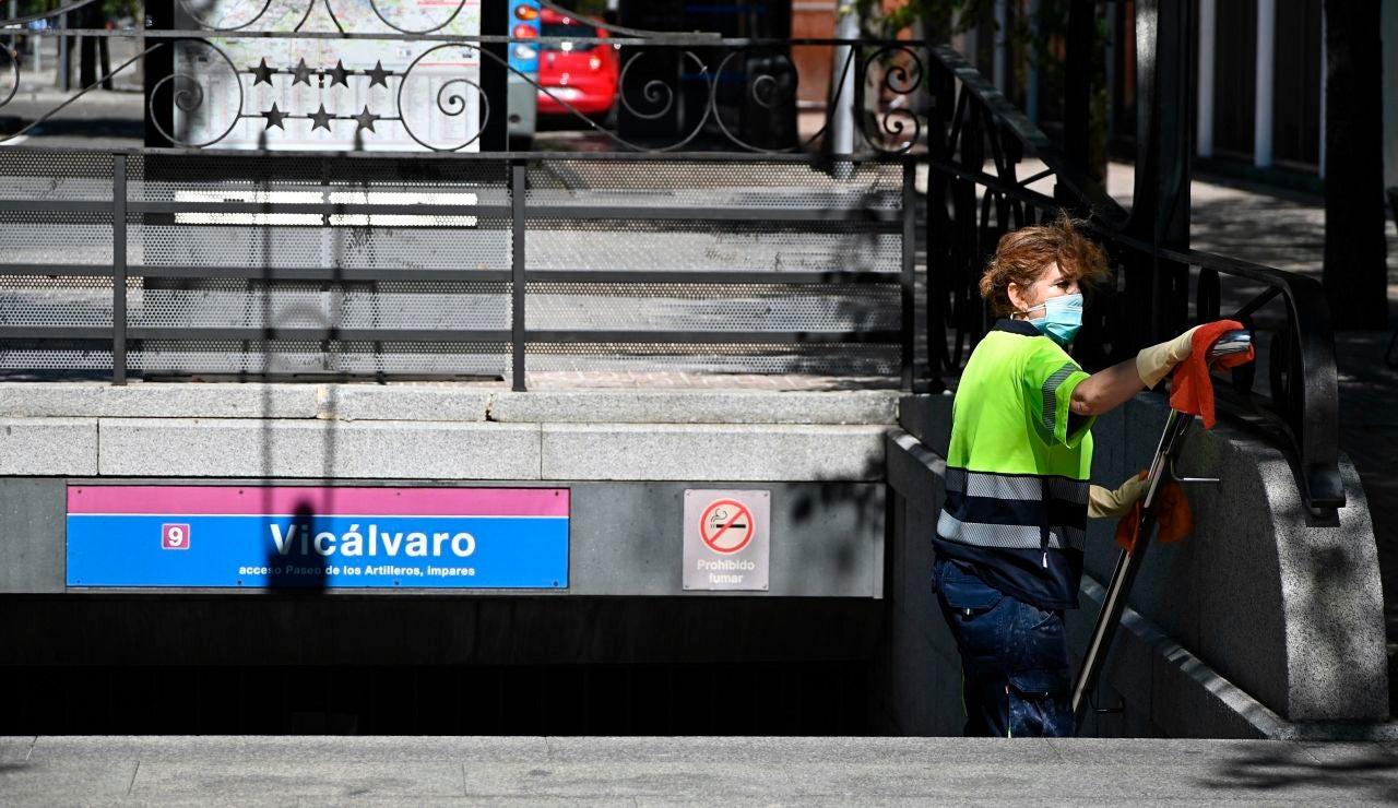 Una operaria limpia la barandilla de acceso del metro del barrio madrileño de Vicálvaro