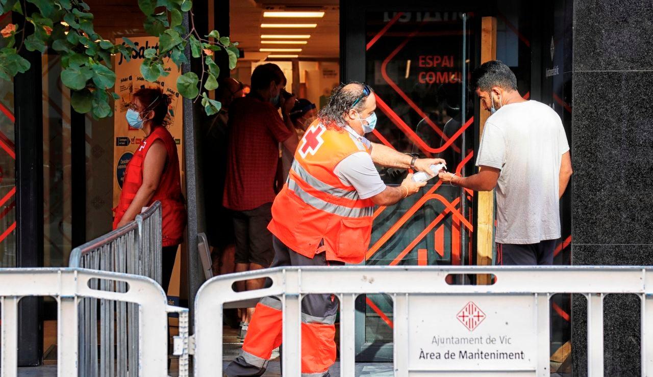 Un voluntario de la Cruz Roja atiende a un vecino del barrio del Remei de Vic (Barcelona).