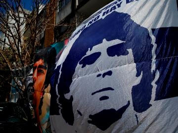 Seguidores despliegan pancartas frente a la clínica donde permanece internado el exfutbolista argentino Diego Maradona