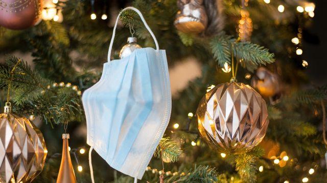 Una mascarilla colgada de un árbol de Navidad