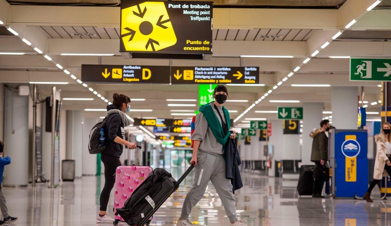 Viajeros caminan por la terminal de llegadas del aeropuerto