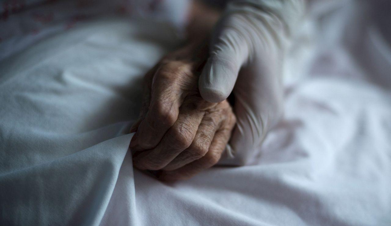 Mano de un sanitario junto a la de un paciente