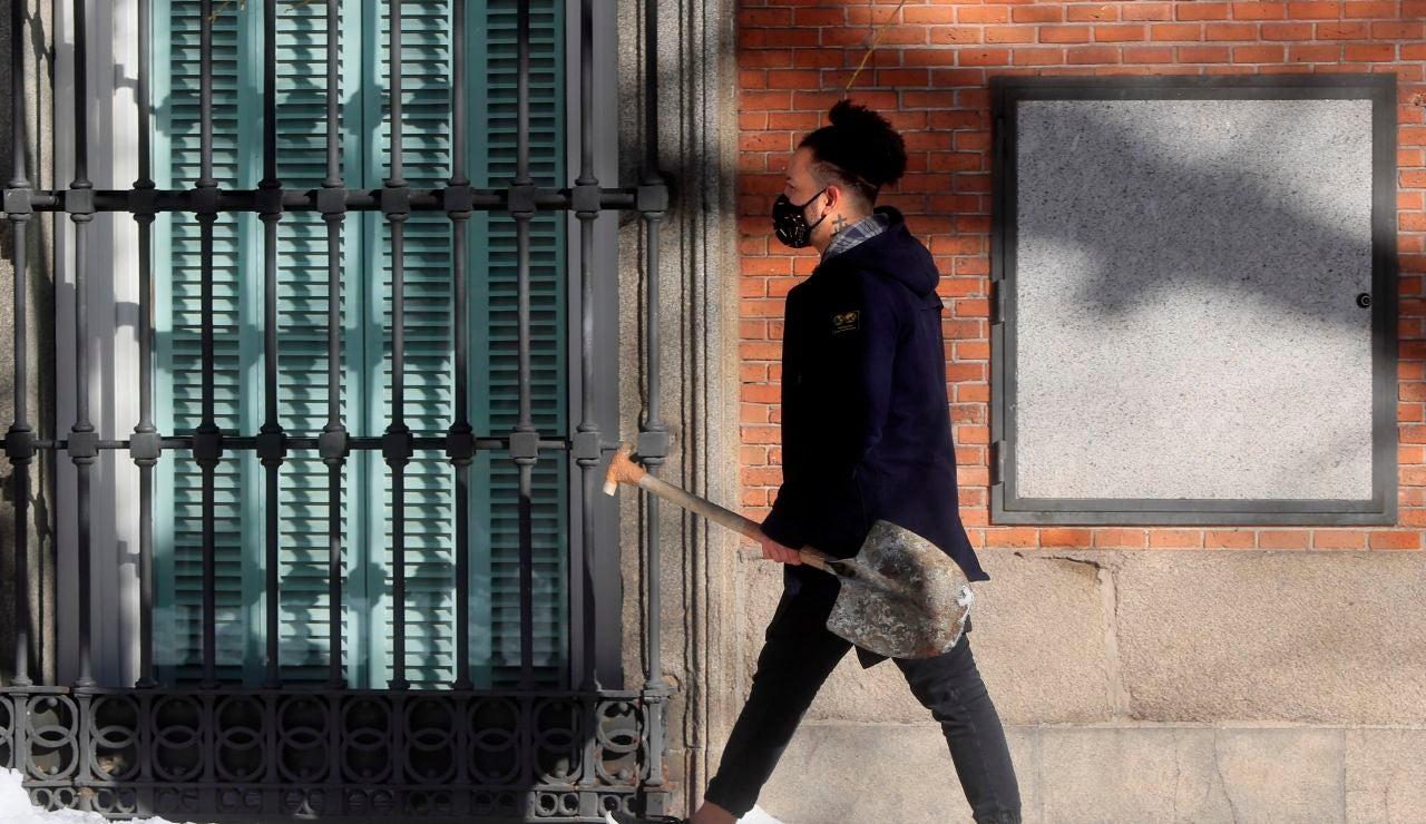 Un joven camina por una calle de Madrid con una pala en la mano