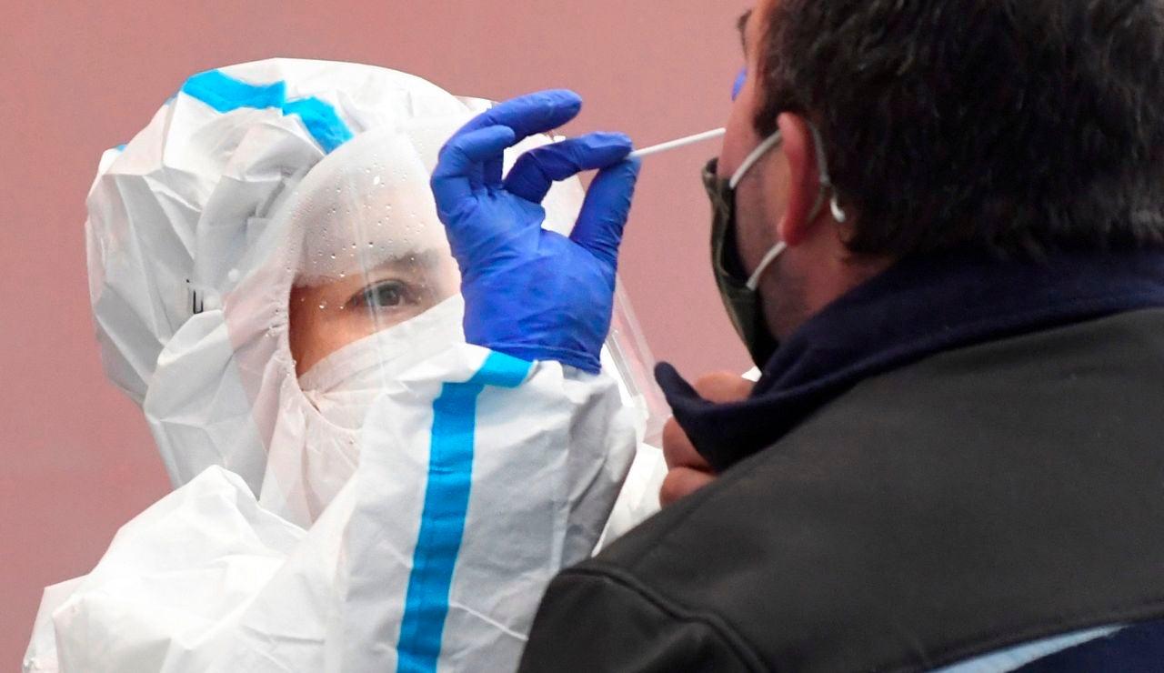Una enfermera realiza una PCR a otra persona.
