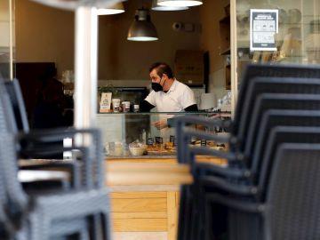 Un hostelero prepara cafés para llevar en una cafetería ante las nuevas restricciones por el coronavirus