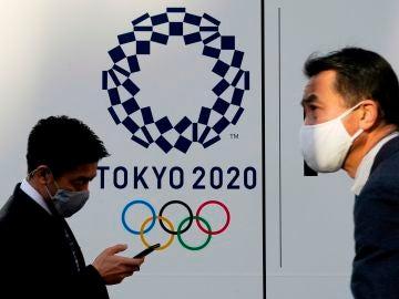 Dos personas pasean con el logo de los Juegos Olímpicos de Tokio 2020 de fondo.