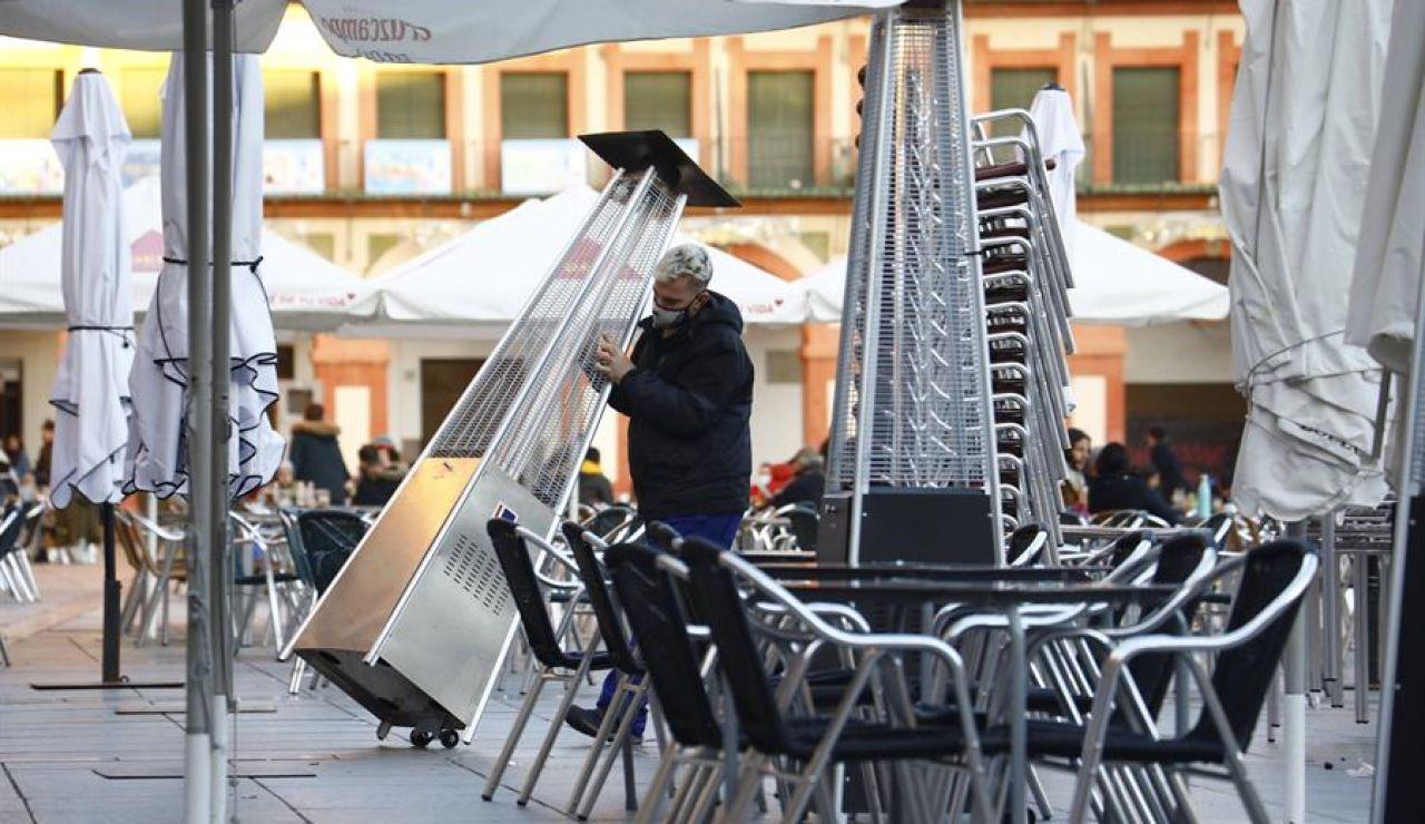 Un trabajador recoge el mobiliario de la terraza de un restaurante.