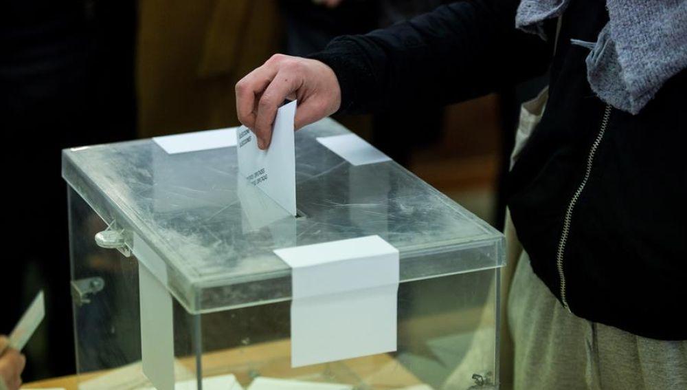 Elecciones Cataluña: Una mujer deposita su voto en una urna en las elecciones