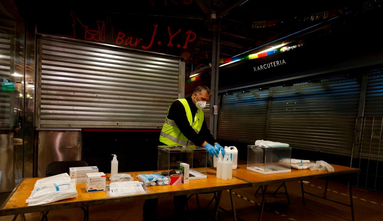 Un operario prepara una mesa electoral de cara a las elecciones en Cataluña del 14 de febrero
