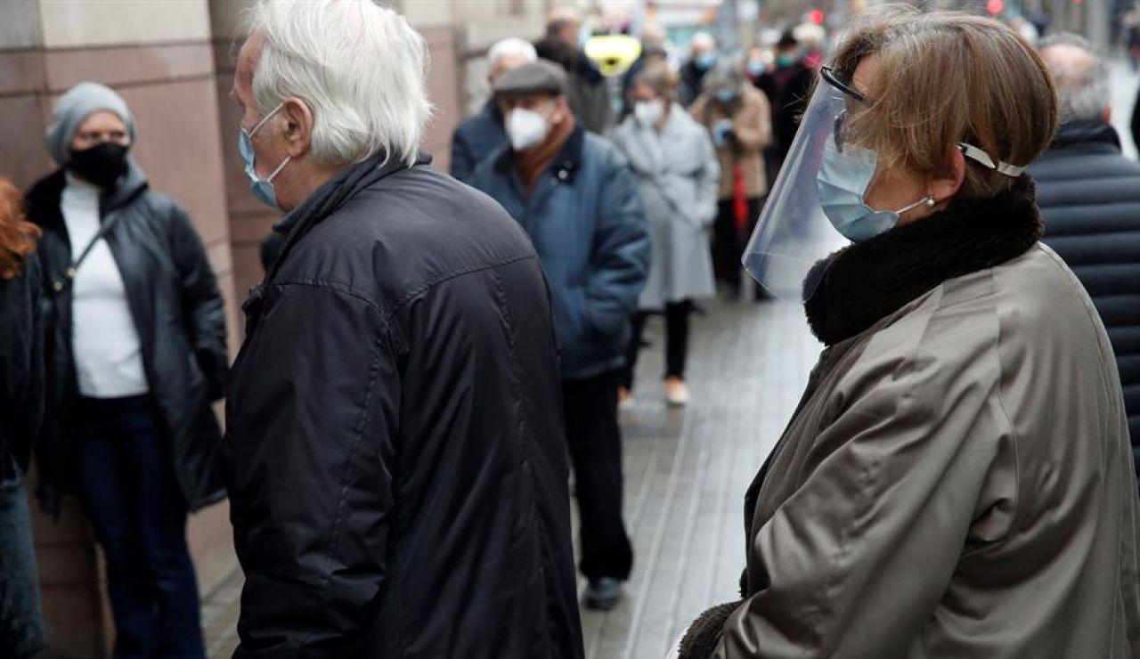 Dos personas mayores esperan su turno para votar en Cataluña.