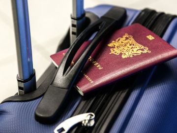 Imagen de archivo de un pasaporte y una maleta