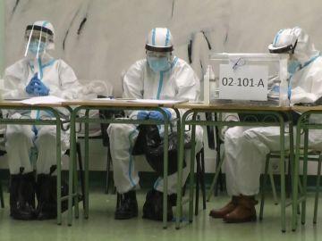 Miembros de las mesas electorales protegidos con los trajes EPI para protegerse de los contagiados de coronavirus en las elecciones catalanas 2021