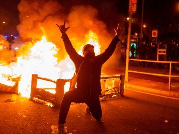 Un manifestante monta una barricada en Barcelona.