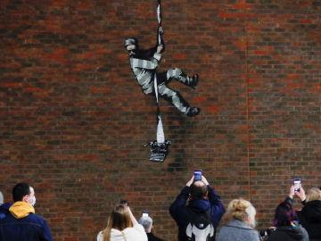 Un grupo de personas toma fotos del nuevo grafiti de Banksy de la prisión inglesa de Reading
