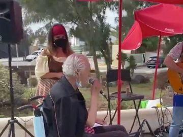 Un anciano en una residencia cantando después de vacunarse contra el coronavirus