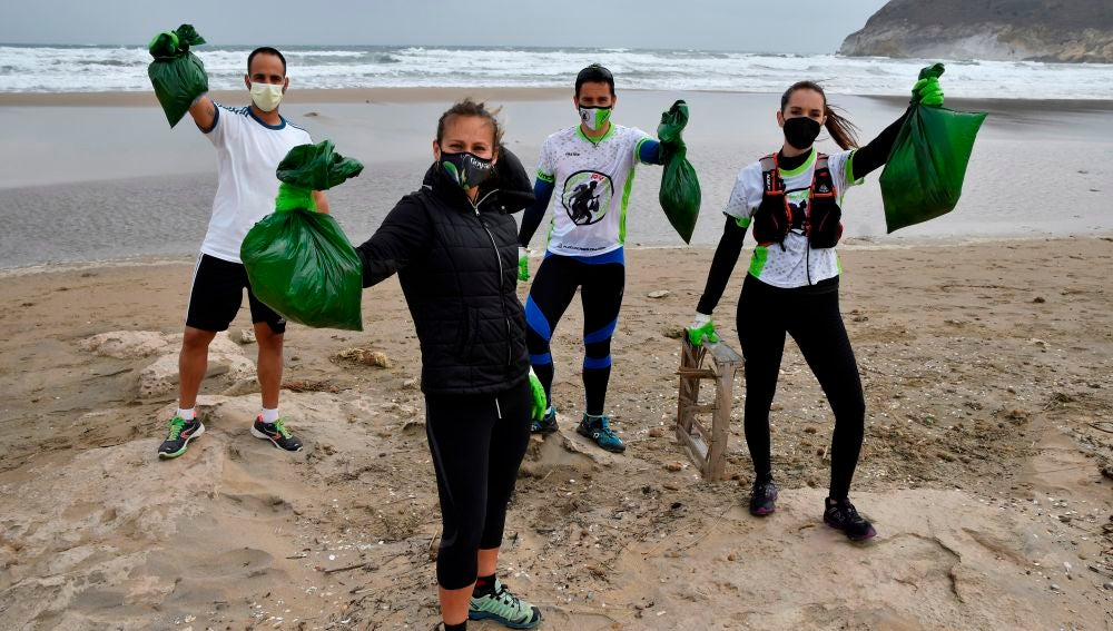 """Miembros del grupo """"Plogging RRevolution"""" recogiendo basura en una playa"""