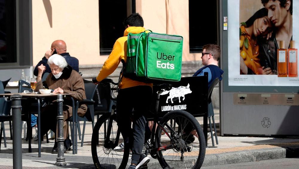 Un repartidor de Uber Eats aguarda junto a un establecimiento de hostelería en Madrid