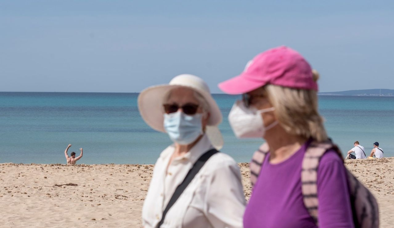 Dos turistas caminan por el paseo marítimo de la playa de Palma de Mallorca