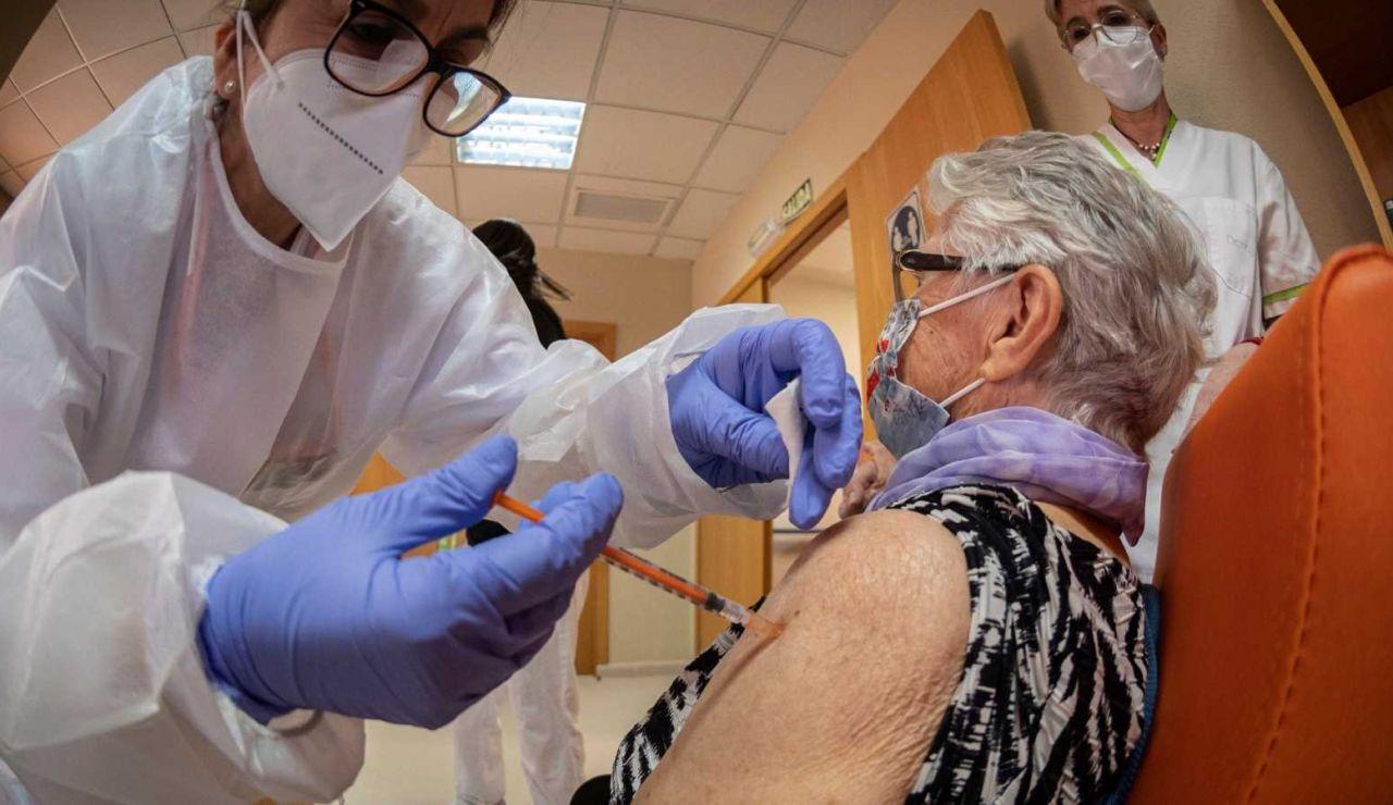Sanitario vacuna a una persona mayor