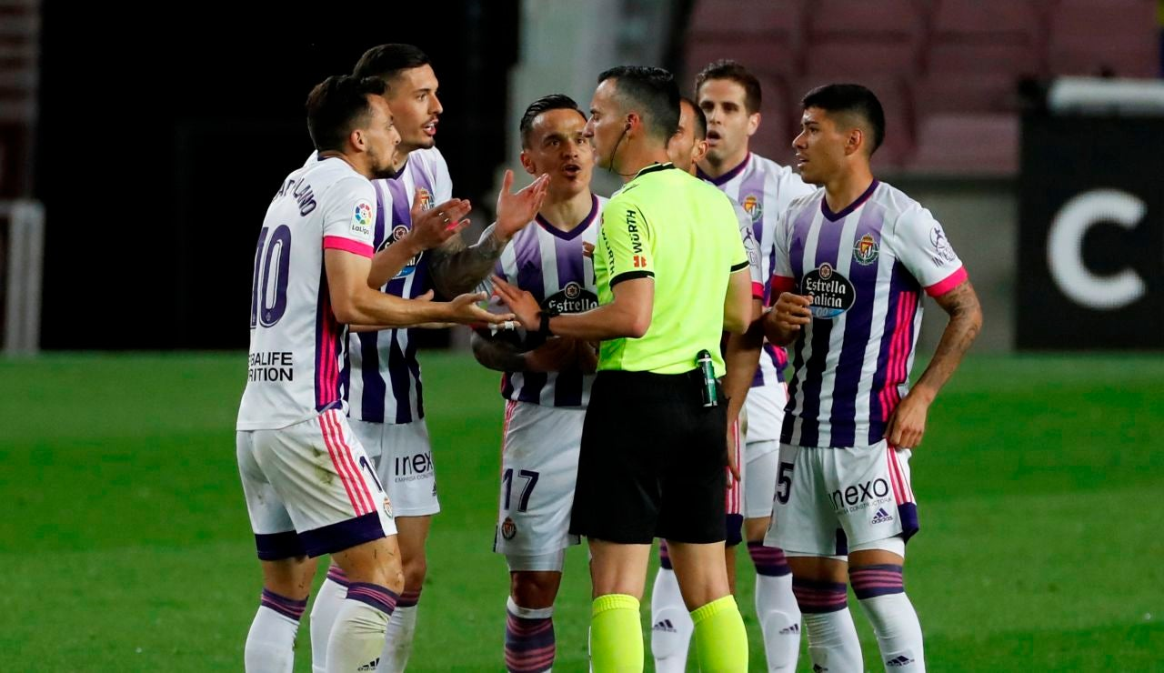 El árbitro Jaime Latre conversa con los jugadores del Real Valladolid