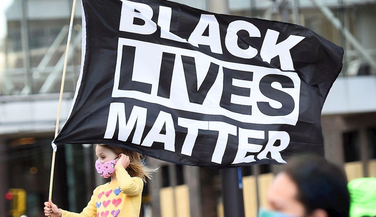 """Una niña sostiene una bandera en la que se lee """"Black Lives Matter"""", el eslogan utilizado en las protestas motivadas por la muerte de George Floyd"""