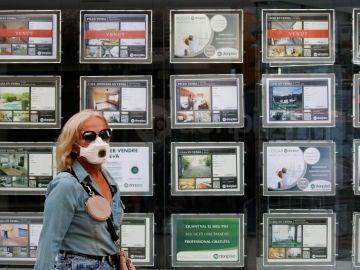 Una mujer pasa por delante de carteles de alquiler