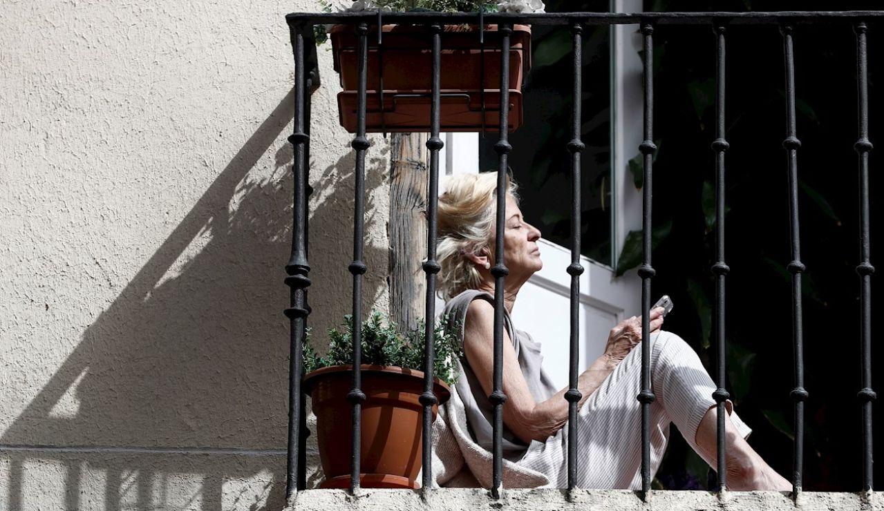 Una mujer toma el sol en el balcón de su casa en Madrid durante el confinamiento