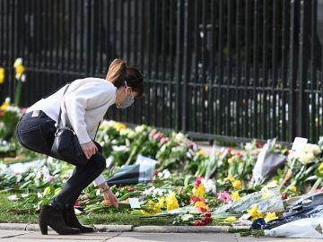 Una mujer deposita una ramo de flores frente al Castillo de Windsor tras la muerte del Duque de Edimburgo
