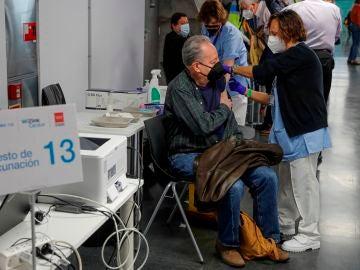 Una persona recibe una dosis de vacuna en el Wizink Center de Madrid
