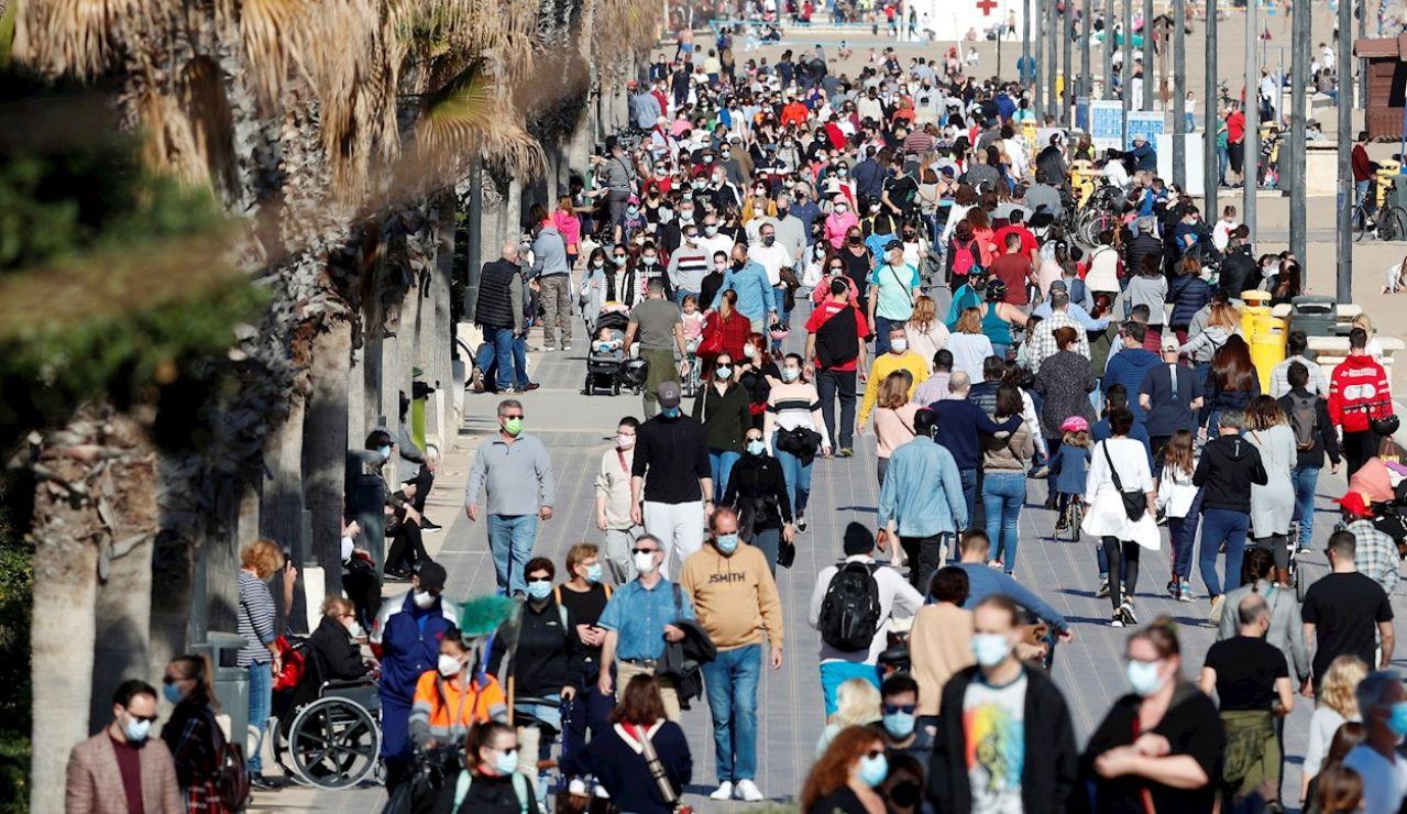 Decenas de personas pasean por el paseo maritimo de playa de la Malvarrosa, en Valencia