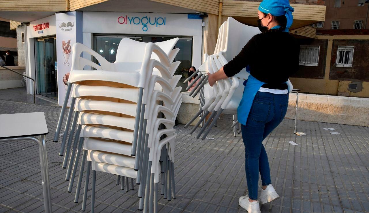 Camarera recogiendo la terraza de un bar